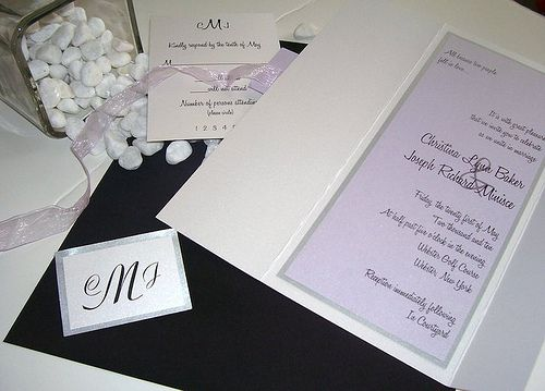 Lilac Love by This & That Creations: This long sleek invitation in nothing less than stunning. The invite is printed on a light lilac shimmer paper, backed with a silver shimmer paper and adhered to a white shimmer jacket. The jacket will be wrapped with a delicate sheer lilac ribbon and have a tag displaying your monogram or wording of choice. The reply card and reception card can be placed inside the jacket or tucked behind the ribbon.