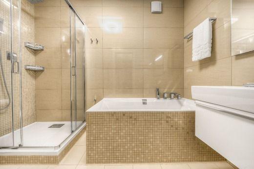 Современный дизайн ванной комнаты в светло-бежевых тонах. Большая душевая зона с поддоном прямоугольной формы и стеклянными перегородками. Ванная в едином стиле с душем. #поддон_для_душа #стеклянная_перегородка_для_душа #квадратная_ванная