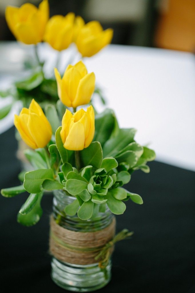Accented with twine for a rustic touch these simple centerpieces feature yellow tulips and green succulents.