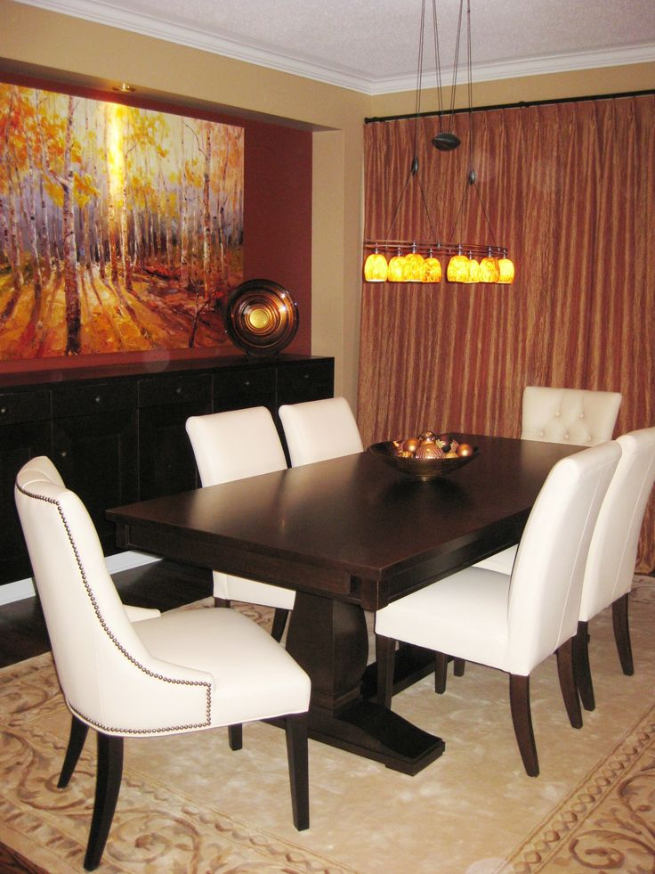 Warm luxurious earth tones envelope this whole dining room. Rich dark wood table and large serving cabinet ground the space. Cream coloured leather chairs pop against the heavy table to lighten the space.