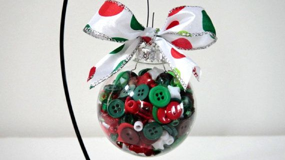 "What a cute ornament for Christmas decorating! A 3"" diameter glass clear ball filled with red, green and white buttons and beads. Finished with a 1"" white, red and green polka dot wired ribbon with a silver edge."