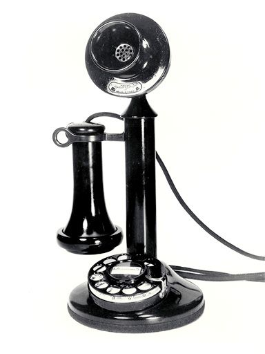 Candlestick telephone with a carbon microphone (transmitter), and a side switchhook upon which an ear piece (receiver) was placed when not in use. (late 1890s to the 1930s)