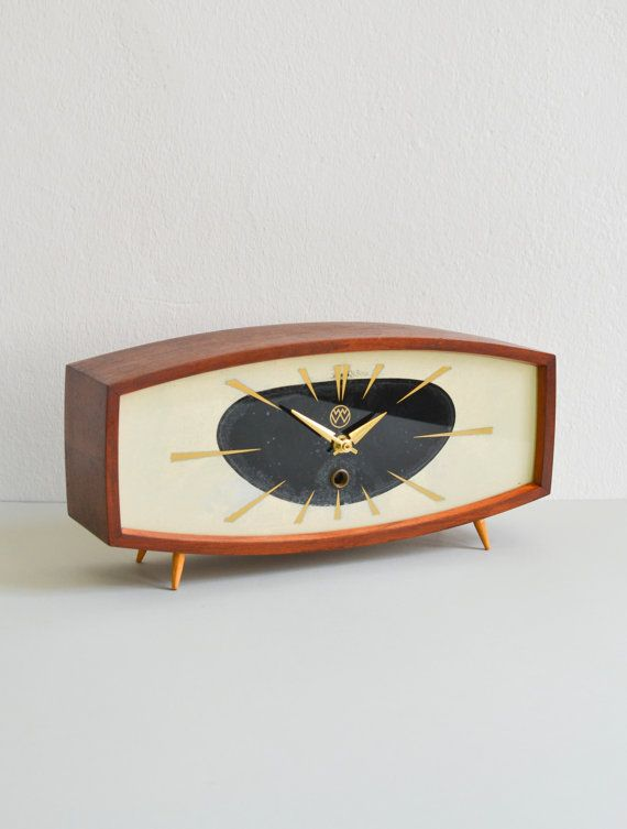 Vintage Weimar Mid-Century Modern mantel clock from the GDR  This very elegant Mid-Century Modern mantel or table clock is made of a teak wood and is equipped with a sleek designed black and white clock face with brass hands. I love the rich colored teak wood and the super modern East German design so typical for the era (even with the little tapered legs that were so 60s).  Weimar clocks are my most favorite clocks to collect. They had the most marvelous designs of the era. The clockwork…