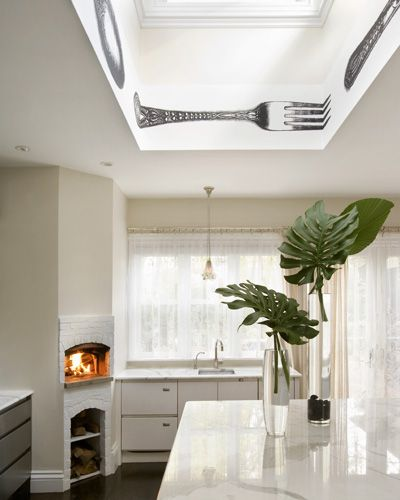 I love the fireplace in this kitchen, and the sheer window treatments were specifically chosen to counteract the stark modernity.  Such a cool idea.
