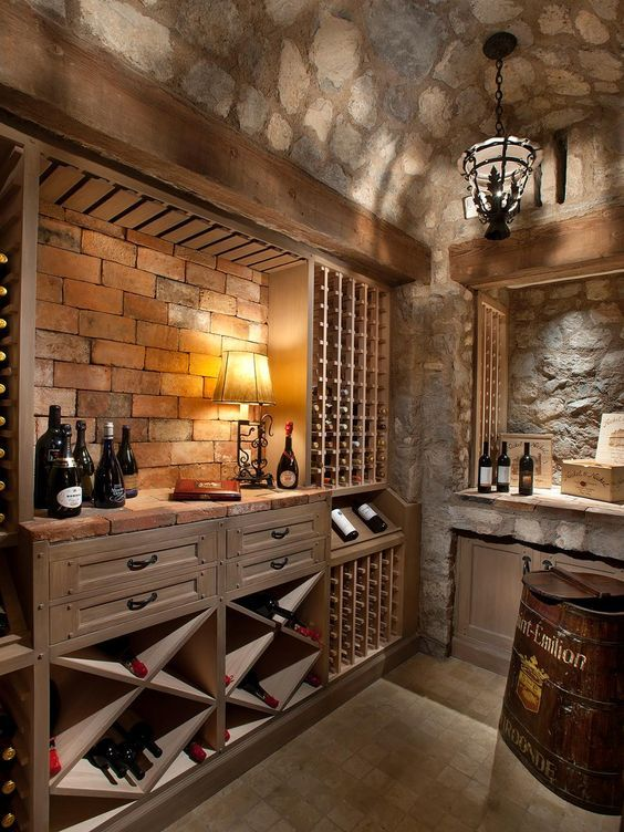 Stone, brick, and wood combine to create this neutral wine cellar filled with rustic charm. A metal pendant light hangs from the ceiling adding to the rooms old world feel.: