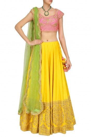 Neha Saran a yellow lehenga in silk base with zari and dori embroidery all over the ghera. It is paired with a hot pink embroidered blouse and parrot green net dupatta.