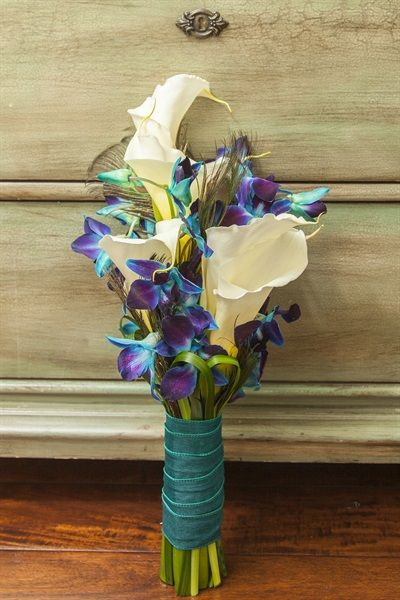 Small bridesmaid's bouquet with calla lilies, blue dyed orchids, and peacock feathers.