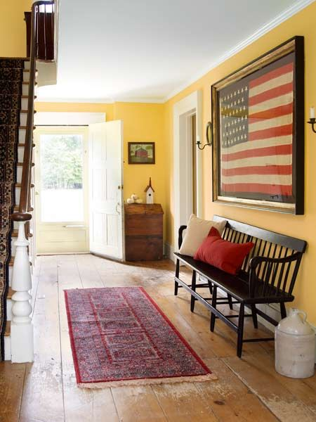 Wide-plank wood floors, a welcoming bench and vintage flag greet visitors to this pre-Civil War farmhouse. | Photo: Tria Giovan | thisoldhouse.com