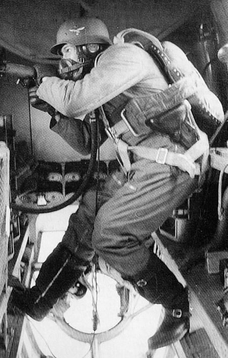 A Luftwaffe dorsal gunner on a Heinkel He-111 bomber manning an Mg15 and he is equipped with an RZ20 parachute and an M42 Luftwaffe Stahlhelm. In many German bombers of the war, just one man was tasked with operating three or more defensive positions, making it impossible to effectively protect the whole aircraft in case of an attack from multiple sides. Note his P.08 Luger holster, possibly issued by Krieghoff, the manufacturer-supplier to the Luftwaffe.