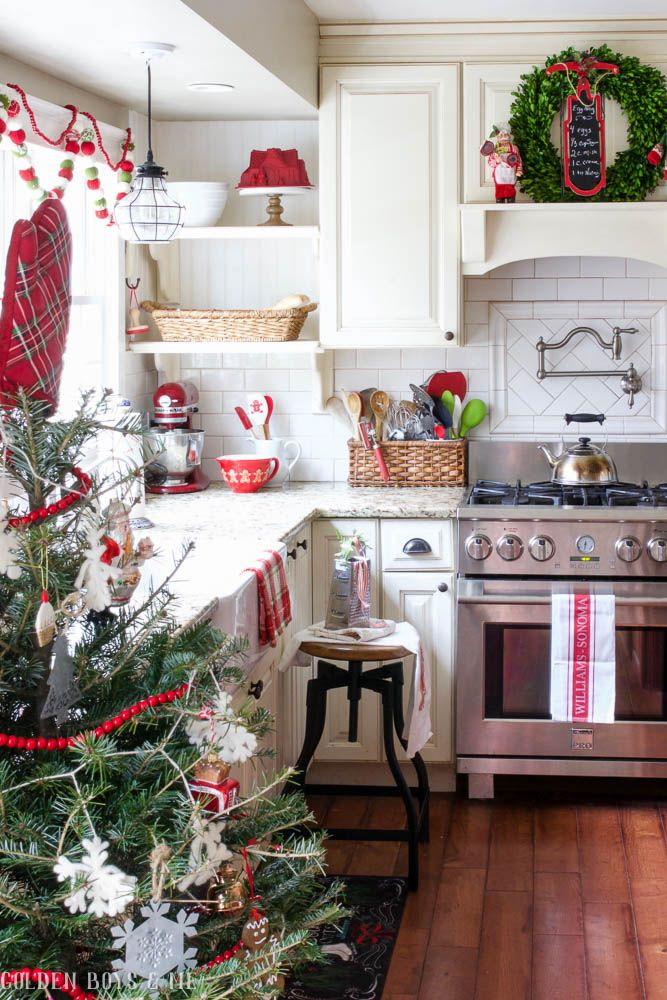 Farmhouse style kitchen with red accents and boxwood wreaths as Christmas decor. I've never seen a Christmas tree in a kitchen before!!