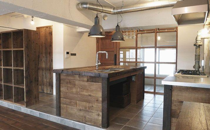 <p>天板も側面も古材貼りのキッチン。工業用照明に負けない重厚感。</p>