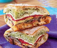 Mediterranian Pressed Picini Sandwich  This sandwich turns take-along food flaws--travel time, cramped packing quarters, moist ingredients--into assets. Pressing the sandwich lets the crusty bread soak up roasted vegetable juices, and travel time gives flavors a chance to meld.