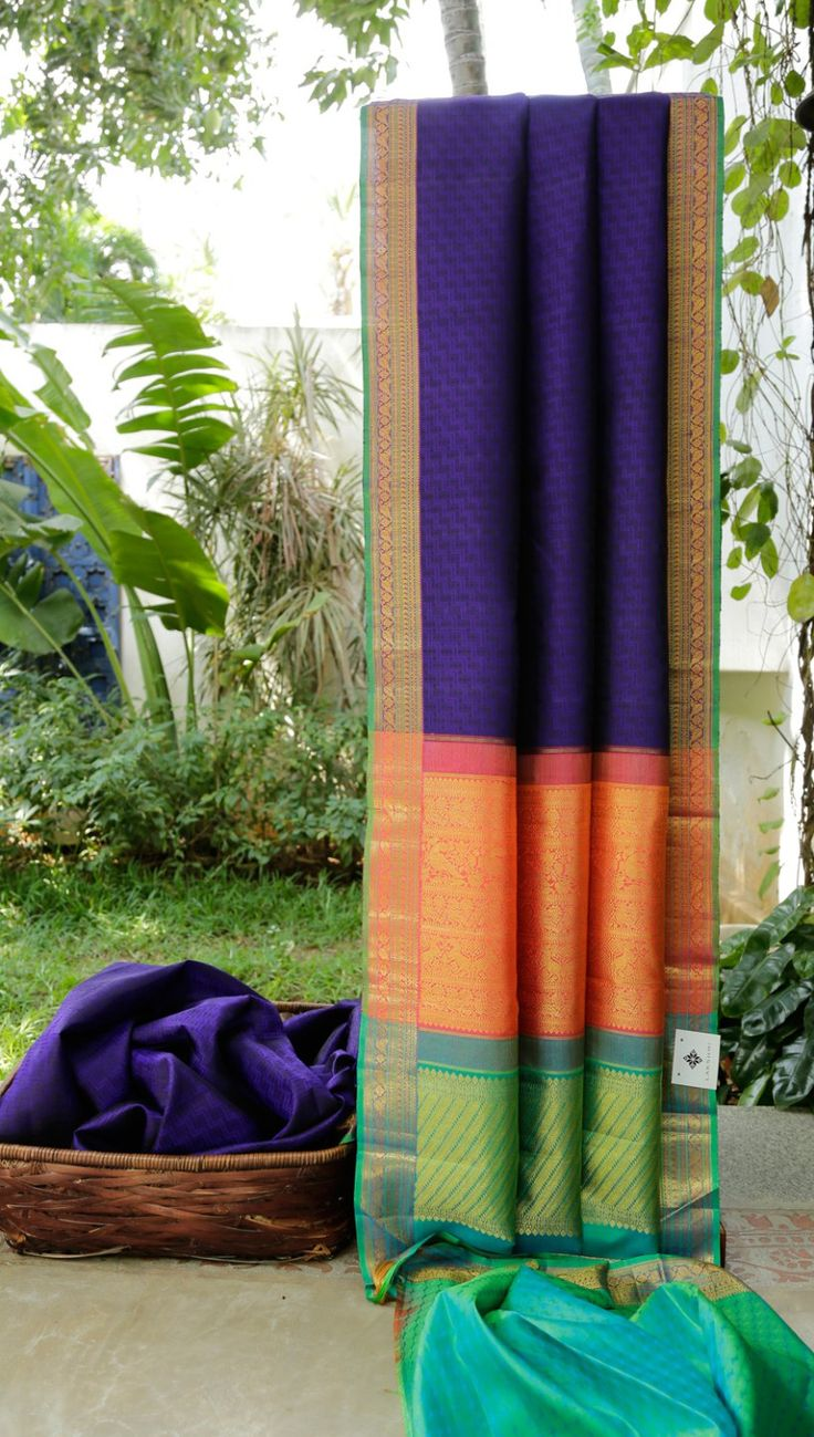 This kanchivaram silk is in midnight blue with a geometrical pattern in berry blue thread brocade. the border is in violet and fern green with gold zari work. The pallu has a strawberry pink band a…