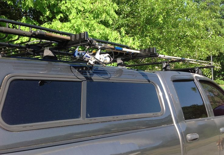 Lockable surf rod or fishing pole holder on the roof rack for Fishing rod roof rack