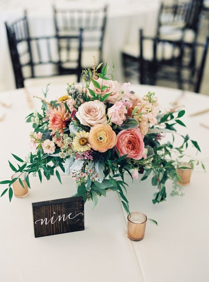 Rustic ranunculus and rose wedding table centerpieces: http://www.stylemepretty.com/little-black-book-blog/2016/11/28/big-sky-montana-destination-wedding/ Photography: Simply Sarah - http://simplysarah.me/