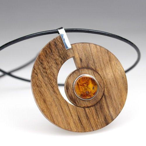 Oryginalny wisior z afrykańskiego drewna AMAZAQUE,  BURSZTYNU BAŁTYCKIEGO i SREBRA. Zawieszony na lakierowanym, czarnym rzemieniu z zapięciem. Połączenie naturalnych materiałów i nowoczesnego wzornictwa.  Wysokość wisiora około 58mm, długość rzemienia 45cm (możliwość zmiany długości rzemyka według życzenia).   Czas wykonania: ok. 3-4 dni. Ze względu na wykonanie z materiału naturalnego (drewno, bursztyn etc.) zamówiona praca może się różnić od przykładowej, prezentowanej na zdjęciu kolorem…