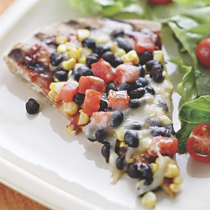 The secret to a grilled pizza is having all your ingredients ready to go before you head out to the grill. Make it a meal: Toss the extra black beans, diced tomato and some avocado with prewashed salad greens and a tangy vinaigrette and dinner is on the table in no time.