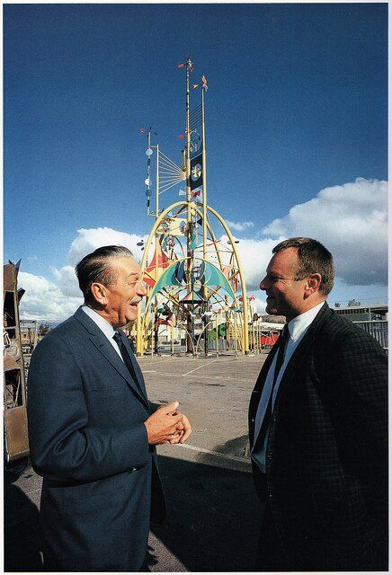 Walt and Disney Imagineer Rolly Crump in front of the large kinetic sculpture The Tower of the Four Winds created by Crump as a marquee showpiece for the exterior of the It's a Small World building at the 1964 New York World's Fair
