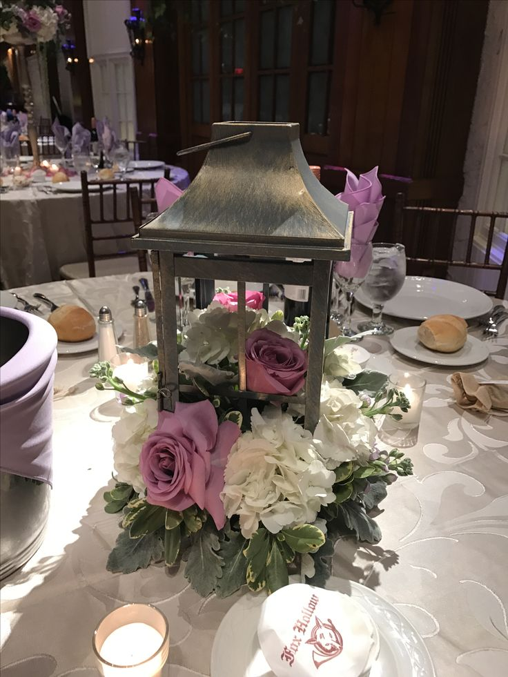 Lantern wedding centerpiece with an arrangement of white hydrangea, Cool Water roses, Apple Blossom stock, dusty miller and variegated pitt. Fox Hollow