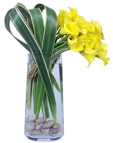 Yellow Callas and varigated flax make this a unique table arrangement.  Love the river rocks. By Flower Factor