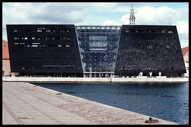Library in Copenhagen  The Sun reflects in the water and the water reflects in the black glass making the wall looks like magic