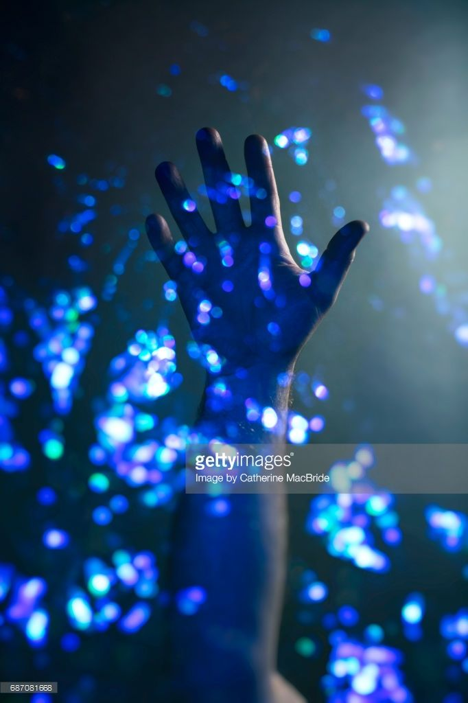 a hand reaches up through a multitude of twinkling lights