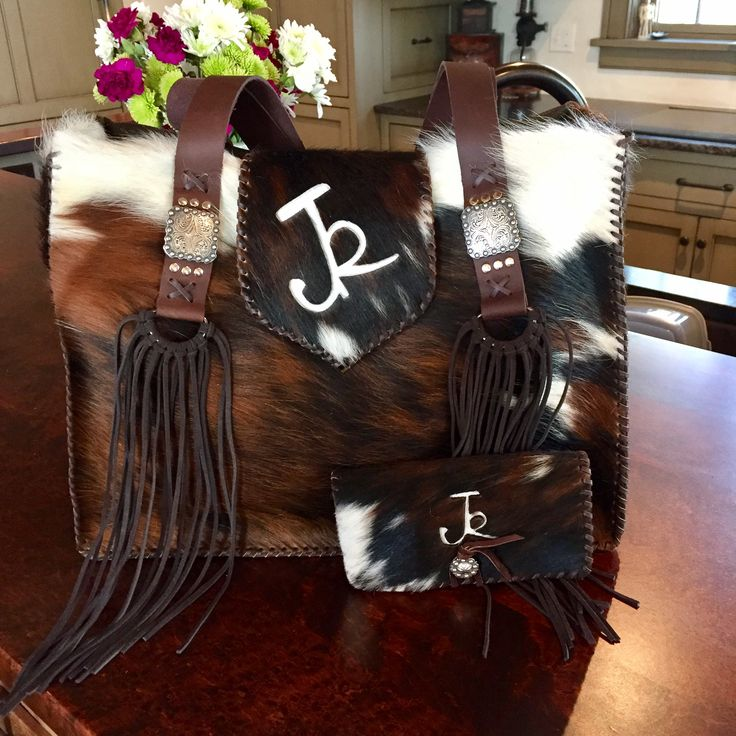 The Buckaroo Tote with matching checkbook case in tricolor cowhide, stitched in brown leather lace with the owners brand in white hair on hide.  Custom purses and totes from gowestdesigns.us