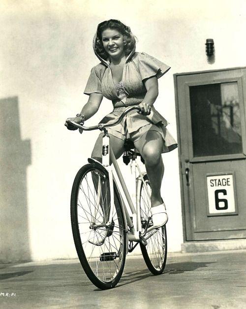 Martha Raye rides a bike.