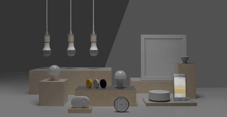 Ei hånd holder en fjernkontroll som kan dimme lyset uten fast installasjon. I bakgrunnen er det to bilderammer og ei bordlampe.