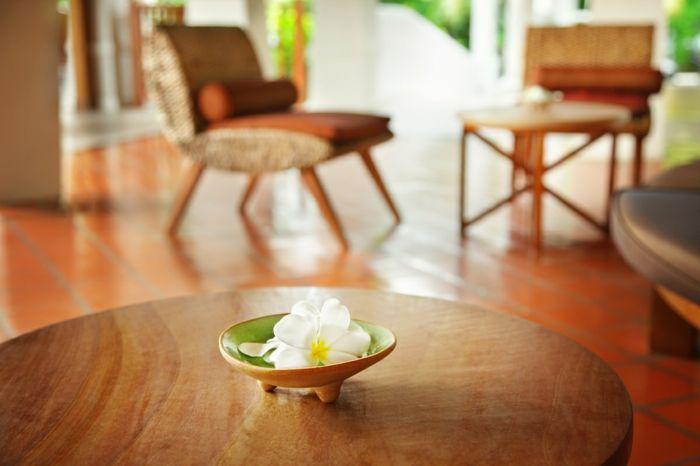 deco ethnique, bouddha zen, deco zen, table ronde en bois, bol avec orchidée blanche et jaune, deux fauteuils en style ethnique, carrelage en orange