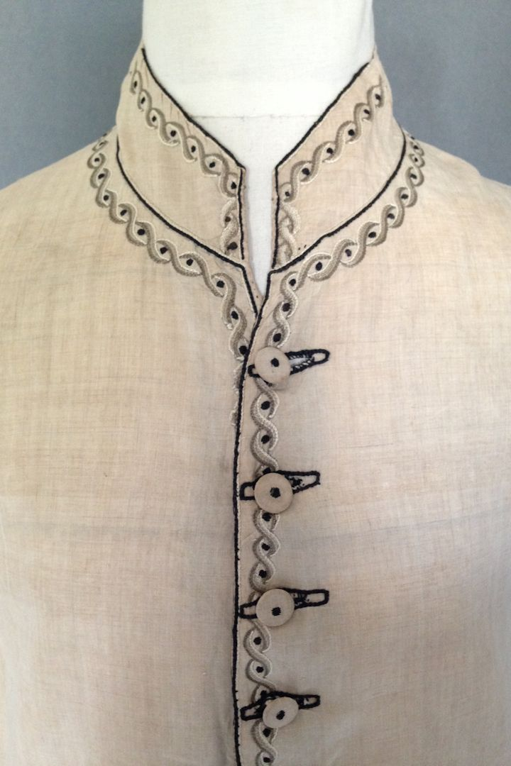 Detail, waistcoat, 1790s. Natural coloured linen with tambour embroidery in a guilloche design in four shades of sage green through neutral, interspersed with a black spot, round the collar and neck, down the front and along the bottom of the waistcoat, also on the pocket edges, self covered buttons with embroidered black centre spot, black embroidered buttonholes, cotton lined with black silk edging, the back with a coarse natural linen.