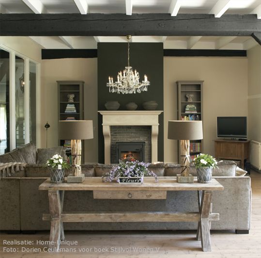 Greys and browns, rustic and modern. Love the idea of how to decorate a sofa table. Love the dark accent wall on the fireplace.