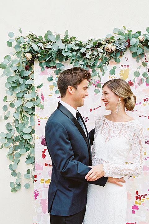 San diego wedding shoot at estancia hotel bride long sleeve lace gown with high neckline and sweetheart neckline underneath sheer lace with groom navy blue tuxedo with black pants and white dress shirt with long black skinny tie holding red floral bridal bouquet hugging