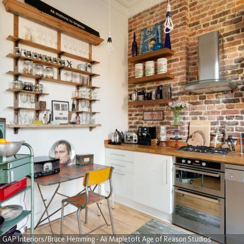 Die Backsteinwand ist das Stil-Statement der Küche. In Kombination mit Vintage-Möbeln und Metallelementen entsteht ein rustikaler Industrie-Look.
