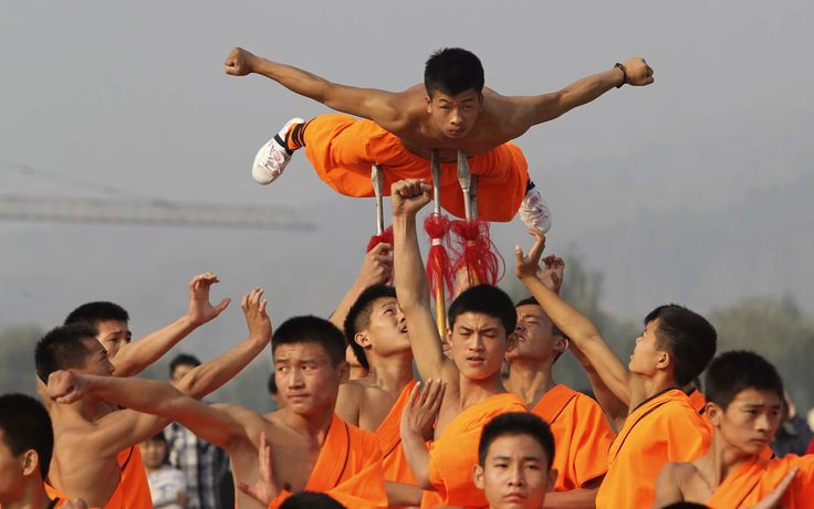 Estudantes de artes marciais shaolin fazem apresentação, um deles sendo erguido por lanças espetando seu corpo, no Templo Shaolin em Dengfen...Em 14/10/2013.