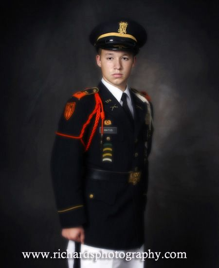 Boy wearing school military uniform for his senior portrait. Taken in a studio with a mottled background.