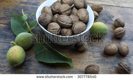 Whole, cracked and green walnuts on wooden table and in white bowl, for display.
