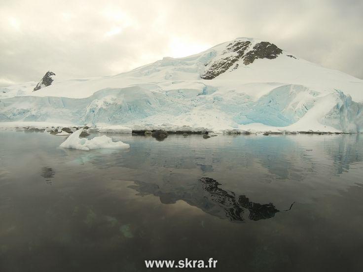 Reflet d'une montagne enneigée dans les eaux d'Antarctique
