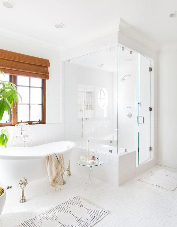 Stunning spa-like master bathroom is equipped with a silver claw bathtub placed on white hex floor tiles and finished with a vintage style hand held tub filler mounted beneath a window accented with stained moldings and a bamboo roman shade.