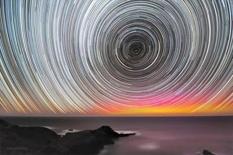 【1.星の軌跡とオーロラ、オーストラリア】     オーストラリア南東部のモーニントン半島で、長時間露光でとらえた星たちの軌跡。オーロラに輝く地平線も美しい。天文学の教育プロジェクト「The World at Night(TWAN)」のWebサイトに投稿された作品    Photograph by Alex Cherney, TWAN