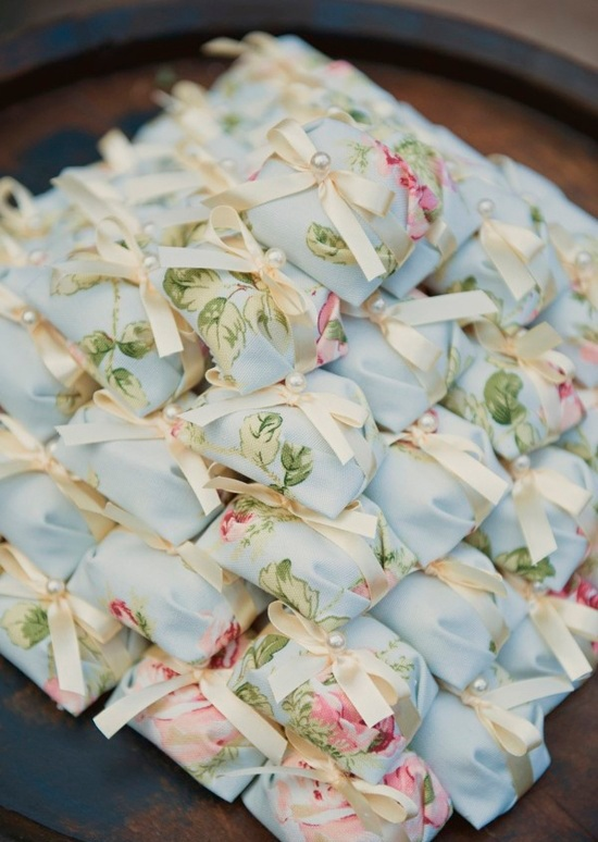 Bem casados envolvidos em tecido azul claro florido e arrematados com fitas de cetim na cor champagne.