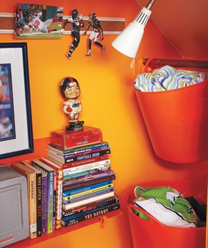 "Bright Laundry Baskets    Open bins in can't-miss-it orange keep the parental battle cry (""Pick that up!"") to a minimum. An unused closet bar works as a hamper holder (the bar lifts up, and the tub slides off) and reminds the boys that there's a place for those dirty towels. A previously unused outlet in the closet allows a wall-mounted lamp to shed light on a stack of books."