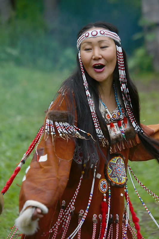 """native american"". Another description for this same image is ""People of Kamchatka, Russia"". I'm an American who can tell you the difference between Chinese, Japanese, and Korean dress and language but not any of the Native American cultures or languages... Sad. I'm leaning towards Russian on her though."