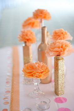 We could find different shaped bottles and paint them gold and use them as centerpieces with single flowers in them.