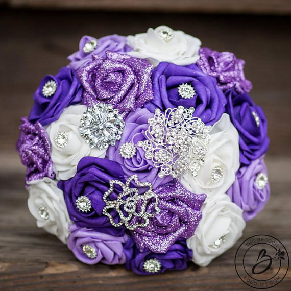"""Purple Majesty"" Lavender Purple And Lilac Wedding Bouquet With Brooches  Romantic and beautiful! This sparkly bouquet is made in shades of the most popular wedding color: purple! Perfect balance of white and shades of light purple (lavender), royal purple and glitter purple roses. Made with our signature Soft-Touch roses for a realistic look and lasting quality! Handle wrapped in white ribbon and accented with rhinestone cuffs and brooch.  Listed: 1 bridal bouquet, total cost (not a…"
