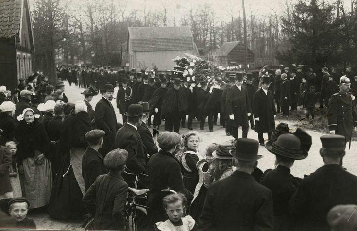 Begrafenis. Begrafenis van Baron Schimmelpenninck van den Oye in Hoevelaken. De kist met het stoffelijk overschot wordt door het dorp gedragen. Voorgrond links: vrouwen in klederdracht. Foto 1914. #Veluwe #Nijkerk #Gelderland #nieuwedracht