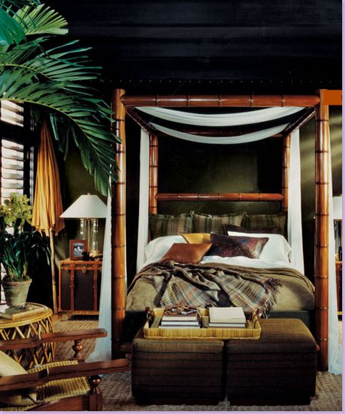 Bedroom: dark green walls, woven rug, bamboo chair, yellow umbrella, chest, plant, tan and white linens, tan ottomans, white canopy, faux-bamboo four-poster bed