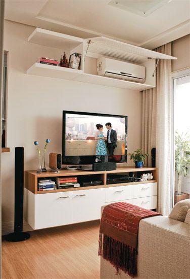O módulo interno do ar-condicionado fica escondido em um armário branco com porta basculante ripada, por onde sai o vento que refresca a sala. Gesso no teto. O forro rebaixado embute pontos de iluminação e delimita ambientes: note como o estar se encaixa em um quadrado marcado no gesso. Além da sala, a Gessobra trabalhou em arremates no quarto e na cozinha. Por R$ 2 580. Home theater: equipamento wireless LGHW554TH, da LG. Fast Shop, R$ 1 437. Quadros Fast Frame. R$ 296 cada.