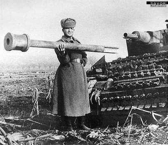 33. Красноармеец держит в одной руке оторванный ствол орудия немецкого танка