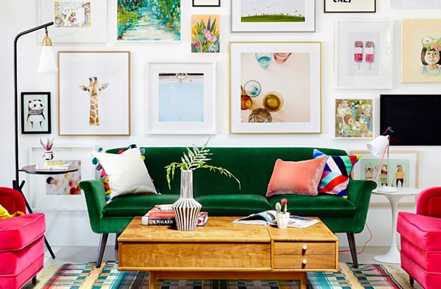 Colour pop living room interior with green velvet sofa, bright pink armchairs and gallery wall. #interiordesign #livingroom #gallerywall